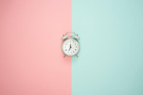 a picture of an alarm clock on a peach and turquoise background